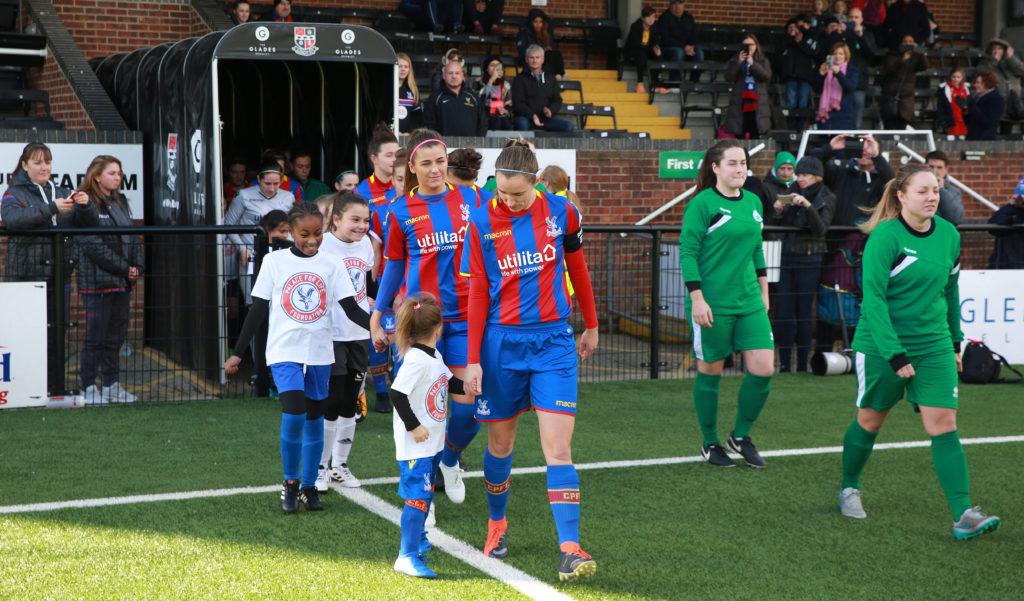 Freya Holdaway of Crystal Palace Ladies walks out with Crystal Palace Ladies mascots wearing Palace For Life Foundation T-shirts