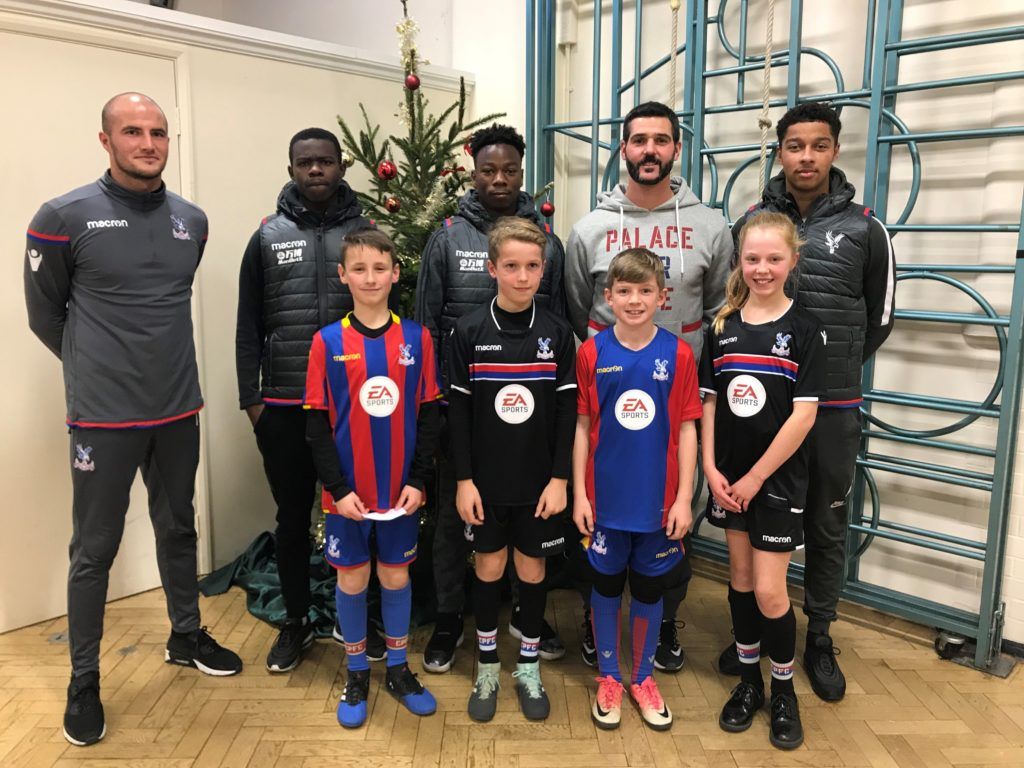 Julian Speroni and three of the Crystal Palace under 23s, as well as Palace for Life Foundation coach Tomasz Krol pose for a picture with children from Rockmount Primary School