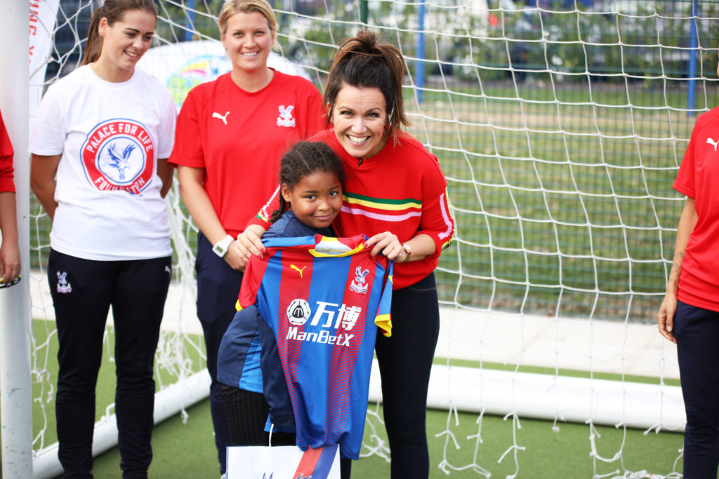 Susanna Reid receives a Palace shirt from a young fan
